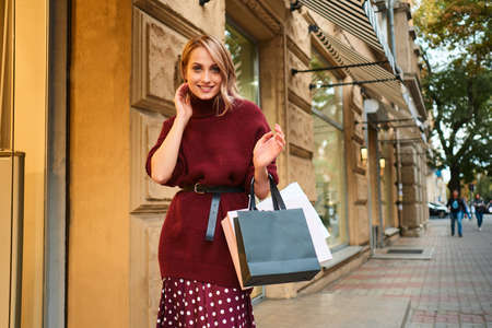 Pretty stylish blond girl in knitted sweater with shopping bags happily looking in camera walking through city street