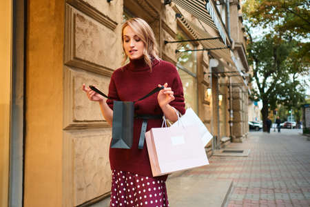 Attractice excited styliah blond girl thoughtfully looking in shopping bag on city street Stock fotó