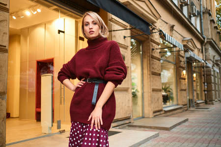 Beautiful stylish blond girl in knitted sweater confidently looking in camera on city street Stock fotó