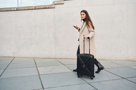 Young stylish businesswoman in coat dreamily walking around street with little suitcase
