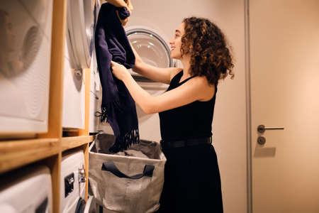 Pretty brunette girl happily loading clothes into washing machine in self-service laundry 版權商用圖片