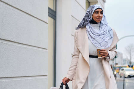 Young pretty Arabic woman in hijab walking around city street with coffee