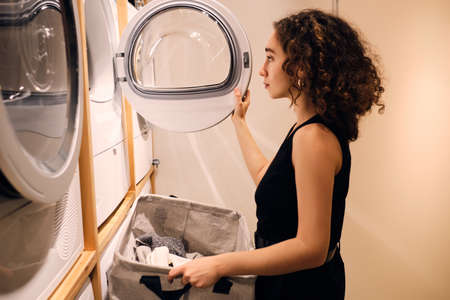 Beautiful girl loading clothes into washing machine in self-service laundry