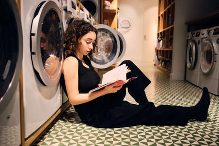 Beautiful brunette girl studying with book while waiting washing in self-service laundry 版權商用圖片
