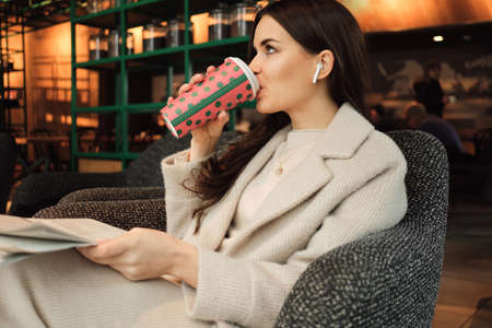 Attractive stylish businesswoman in wireless earphones drinking coffee and reading newspaper in modern cafe Zdjęcie Seryjne