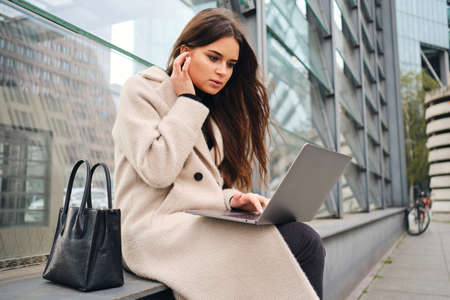 Young attractive casual businesswoman intently working on laptop on city street