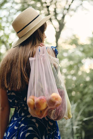 Young brown haired woman in blue dress and hat holding eco bags with fruits and vegetables on shoulder standing from back in beautiful city park.