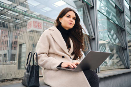 Young pretty businesswoman dreamily working on laptop on city street