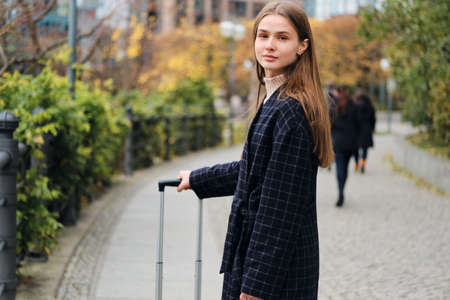 Beautiful casual girl in coat dreamily looking in camera walking around street with suitcase Stock fotó