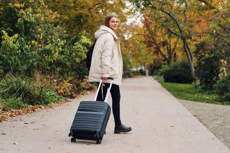 Attractive casual girl in down jacket with suitcase happily looking in camera outdoor