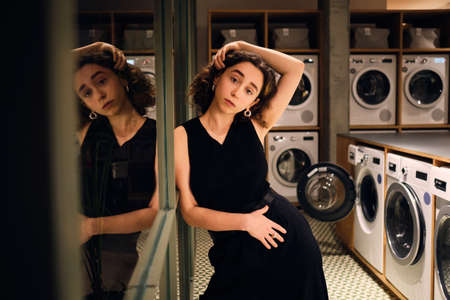 Beautiful stylish girl sensually posing on camera waiting in self-service laundry at night