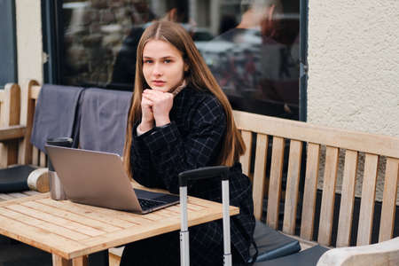 Beautiful casual girl intently looking in camera sitting in outdoor cafe with laptop and suitcase