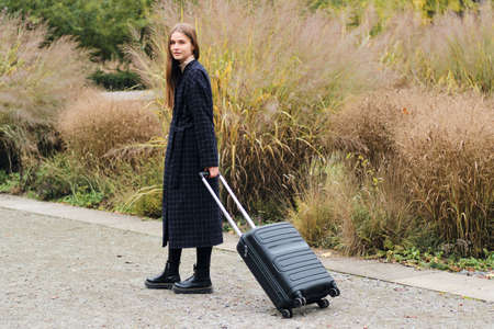 Beautiful stylish girl in coat with suitcase dreamily looking in camera outdoor 版權商用圖片