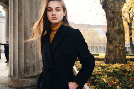 Beautiful serious girl in coat confidently looking in camera in autumn city park