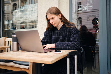 Beautiful casual girl searching place to stay on laptop in street cafe