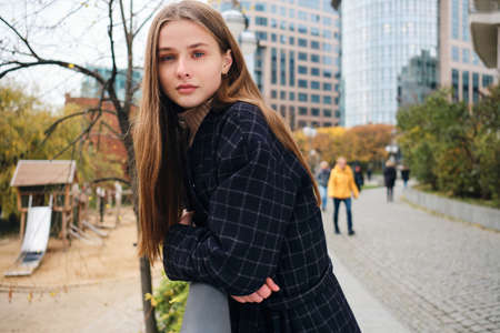 Beautiful casual girl dreamily looking in camera resting alone in city park