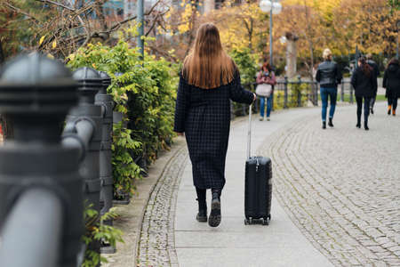 Back view of casual girl in coat walking around street with suitcase