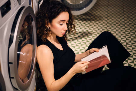 Side view of attractive girl dreamily reading book waiting washing in modern self-service laundry 版權商用圖片