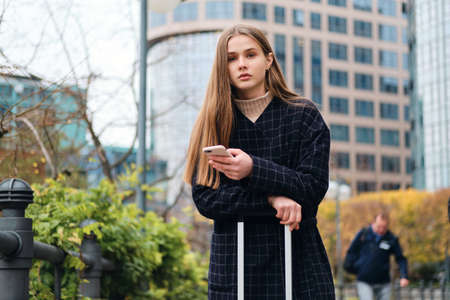 Beautiful casual girl in coat using cellphone standing on city street with suitcase