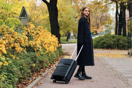 Beautiful stylish girl in coat with luggage bag intently looking in camera in city park