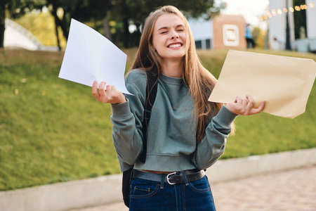 Pretty cheerful casual student girl opening envelope with exams results rejoicing in city park Stock fotó