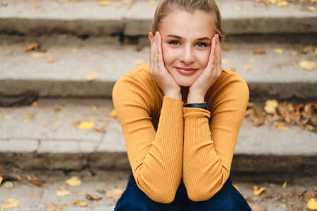 Portrait of cute smiling girl dreamily looking in camera sitting on stairs in park
