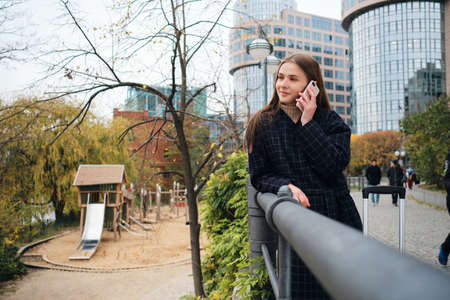 Pretty smiling girl in coat happily talking on cellphone in city park 免版税图像