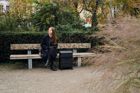 Beautiful stylish girl with suitcase dreamily waiting on bench in city park