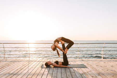 Photo of two beautiful ladies in black sporty tops and leggings training yoga poses by the sea. Young women practicing yoga together with beautiful sea view on background Stockfoto