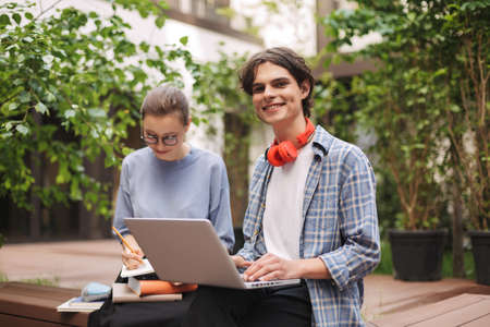 Young smiling man sitting on bench with laptop and happily looking in camera in courtyard of university. Students studying together outdoors Imagens