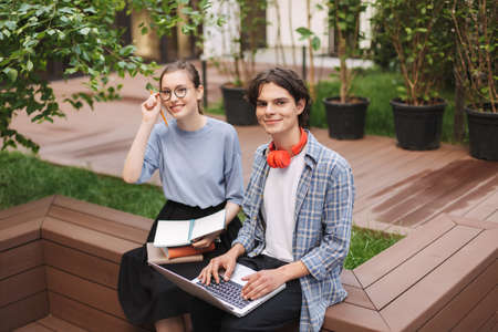 Couple of smiling students sitting on bench with books and laptop and happily looking in camera in courtyard of university. Young man and lady studying together outdoors