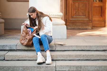 Attractive casual student girl with backpack and textbooks thoughtfully preparing for study sitting on stair of university.