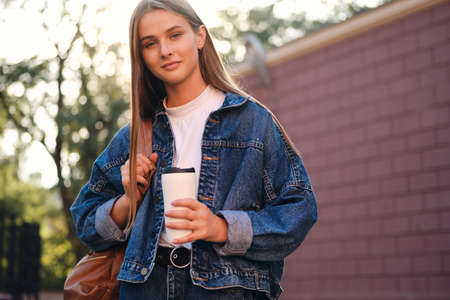 Young beautiful casual student girl in denim jacket with backpack and cup to go dreamily looking in camera outdoor Stok Fotoğraf