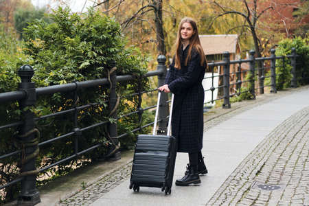 Attractive stylish girl in coat dreamily walking around street with suitcase