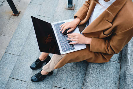 Close up stylish businesswoman in coat working with laptop on stairs outdoor