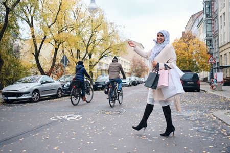 Young smiling Arabic woman in hijab happily walking through city street with shopping bags