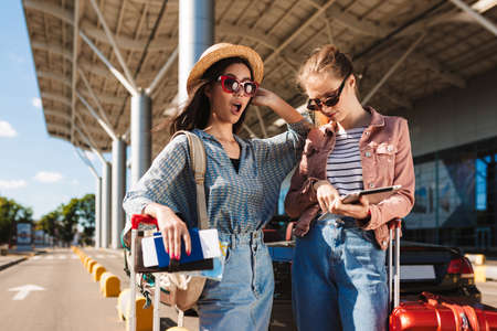 Young female friends in sunglasses amazedly looking in camera holding passport with tickets and tablet in hands with airport on background