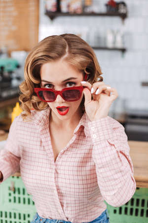 Portrait of pretty girl in sunglasses and shirt sitting at the bar counter and thoughtfully looking in camera in cafe. Stock fotó - 149501628
