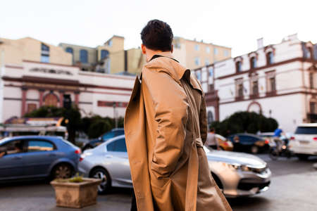 Back view of young stylish man in trench coat walking through city street