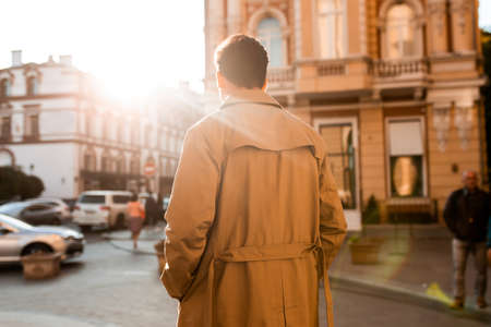 Back view of young confident man in trench coat walking through city street alone