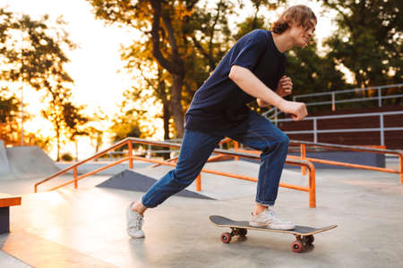 Young cool skater in black T-shirt and jeans riding on skateskateboard at skate park with sunrise on background Standard-Bild