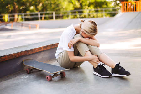 Young skater girl holding her painful leg and crying with skateboard near at skatepark Standard-Bild