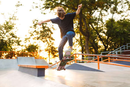 Young cool skater in black T-shirt and jeans practicing tricks on skateboard at skate park