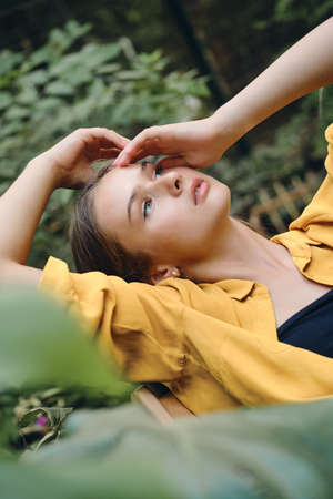 Young attractive woman in yellow shirt holding hand near head dreamily looking up lying around green leaves in park