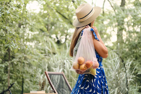 Young attractive brown haired woman in dress and hat holding eco bags with fruits and vegetables on shoulder standing from back in beautiful park
