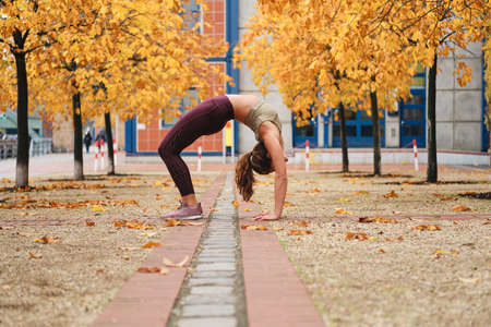 Beautiful sporty girl doing bridge exercise during yoga practice on autumn city street