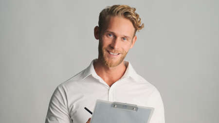 Attractive blond bearded businessman in shirt looking happy working with documents isolated on white background. Successful man