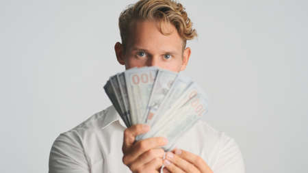 Portrait of young handsome rich bearded businessman looking confident showing wad of money on camera isolated on white background