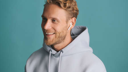 Handsome stylish blond bearded man in hoodie looking happy talking on wireless earphones with friend over colorful background