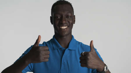 Attractive smiling African American guy happily showing thumbs up on camera isolated on white background. Well done expression